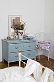 Nostalgisches Schlafzimmer mit hellblauer Vintage-Kommode, verschnörkeltem Gartenstuhl und Metallbett im Vordergrund