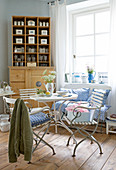 Breakfast table with English garden chairs and old china containers on natural wood shelves