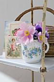 Romantisches Arrangement auf Vintageregal - Anemonen in Blümchenbecher vor nostalgischen Postkarten