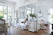 White-painted, wooden partition with glass panels in rustic living-dining room