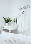 Lacy dresses hanging on wall hooks next to white, rustic dressing table in corner of bedroom
