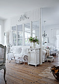 White-painted, wooden partition with glass panels and rustic wooden floor in country-style living-dining room