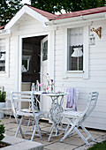White garden chairs and table in front of summer house with white-painted wooden facade