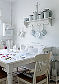 Rustic dining room with white kitchen furniture and collection of vintage milk cans on wall-mounted shelf