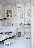 White-painted room in wooden house with metal single bed and vintage-style washstand