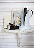 Vintage candlestick and postcard with floral motif on bracket mounted on white wooden wall