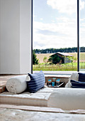 View of old barn across comfortable sunken seating area through floor-to-ceiling panoramic window