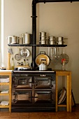 Vintage cooker in simple kitchen unit with integrated wall-mounted shelf and stacked stainless steel saucepans