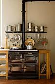 Vintage Küchenofen in schlichter Küchenzeile mit integriertem Wandbord und gestapelten Edelstahltöpfen