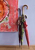 Colourful detail of three walking-stick umbrellas leaning on lavender blue wall next to contemporary painting in hallway