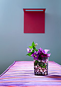 Glass vase of Bougainvillea on red and purple striped cushion; red artwork on dove grey wall in background