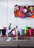 Colourful plastic beakers next to stainless steel sink with running water below souvenirs on pinboard