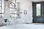 Table with tablecloth and various white chairs in dilapidated room in former factory