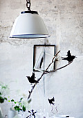 Pendant lamp with white metal lampshade above bird ornaments on twig
