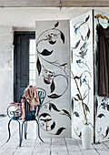 Vintage metal chair next to screen painted with bird motifs