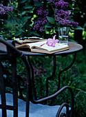 Open book on metal garden table in front of purple flowering lilac