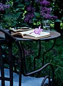 Aufgeschlagenes Buch auf Gartentisch aus Metall vor lila blühendem Flieder
