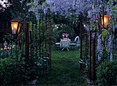 Gartentor unter blau blühender Glyzinienpracht und romantisch gedeckter Gartentisch im Hintergrund