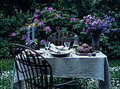 Table in garden set in romantic style with candles and flowers
