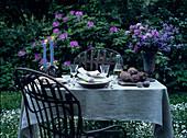 Romantisch gedeckter Tisch mit Kerzen und Blumen im Garten