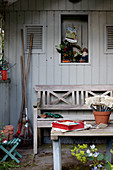Wooden bench in seating area outside garden shed