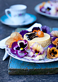 Cream tart on plate decorated with violas