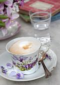 Cappuccino in einer Tasse mit Blumenmotiv