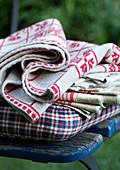 Cushion and folded table linen on garden chair