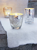 White cloth and silver tealight holders on step