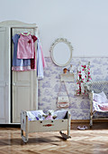 Soft toys in old dolls' cradle and white farmhouse wardrobe in rustic child's bedroom