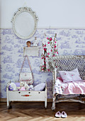 Soft toys in old doll's cradle next to vintage wicker chair against wall with half-height Toile de Jouy wallpaper