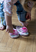 Little girl putting on flip-flops