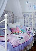 Patchworkdecke auf Himmelbett im Vintagelook vor tapezierter Wand in einem Kinderzimmer