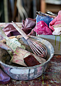Painters' utensils in paint-spattered bowl