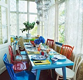 Colorful kitchen chairs in mix of styles around a set dining table