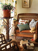 Cozy wicker chair with pillows next to a potted plant on a pedestal