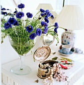Corn flowers in a glass next to an open silver box with jewelry