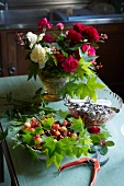 Cherries, a bunch of roses and cutlery on a kitchen table