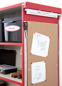 Pinboard and fluorescent tube on side of red tool cabinet