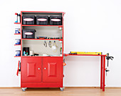 Red converted kitchen dresser on castors with integrated work bench for storing tools