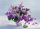 Purple spring bouquet in vase on lace tablecloth