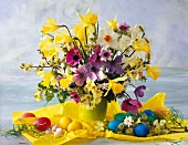 Colourful bouquet with narcissus and Easter decorations on yellow paper