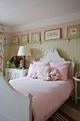 Bed with curved headboard and pink bed linen against light grey wooden wall