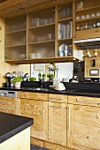 Detail of rustic kitchen units with mirrored splashback