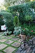 Französisch mediterraner Garten mit Blumentöpfen in einem alten Wägelchen aus gebogenem Draht