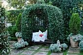 Üppig berankter Bogen einer alten Eisenbank und romantische Zierkissen in französischem Terrassengarten