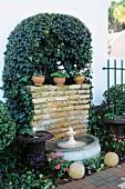 Efeuranken über der Naturstein-Rückwand eines kleinen Springbrunnens