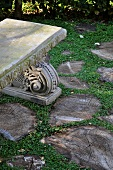 Antique stone bench in the garden and cross sections of tree trunks used as pavers
