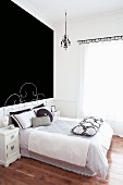 Bed with delicate metal frame against black-painted wall in modern bedroom