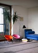 Colourful retro chairs and blue chaise longue in minimalist living room